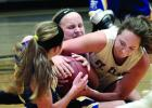 A scramble on the floor found Abby Rost (back) of Minneota, Natalee Rolbiecki (left) and St. Clair's Olivia Drummer fighting for the ball.