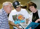 Deb (Bradley) Ahmann, right, above, shows Dennis Broughten, left, and Bob Bossuyt a photo of her brother in a basic training yearbook.