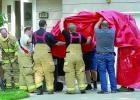 Firemen hoist a tarp at the scene of the fire.