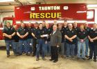 The Taunton Fire Department accepted a check from State Bank of Taunton President Duane Peterson in front of their new rescue truck.
