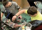 Giving the robot some tweaking were: (left) Logan Schuelke and Ty Lipinski seated and others on the left.